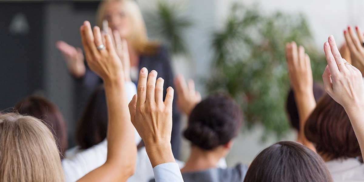 A group of people with their hands up to ask a question at a presentation
